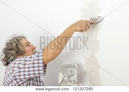 Older Man Plastering A Wall With A Spatula