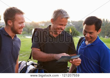 Group Of Male Golfers Marking Scorecard At End Of Round