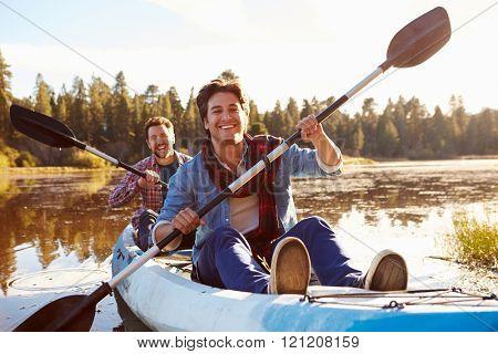 Male Gay Couple Rowing Kayak On Lake Together