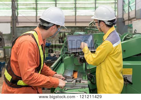 Engineers And Worker Discussing Work Together In Factory