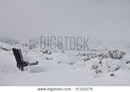 Freshly snow covered wooden bench surrounded by clouds and mountains