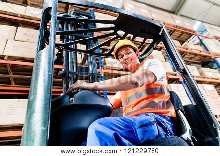 Forklift driver in industrial logistics warehouse looking at the camera