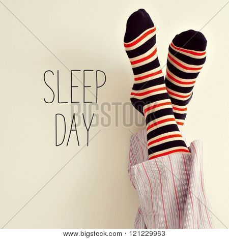 closeup of a young man in pajamas wearing colorful striped socks with his feet against the wall and the text sleep day
