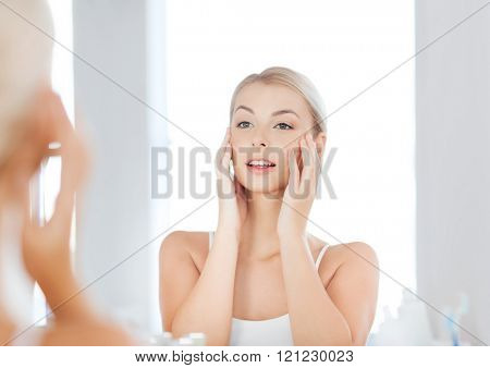 beauty, hygiene, morning and people concept - smiling young woman looking to mirror at home bathroom