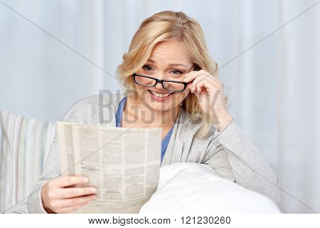 news, press, media, leisure and people concept - woman in eyeglasses reading newspaper at home