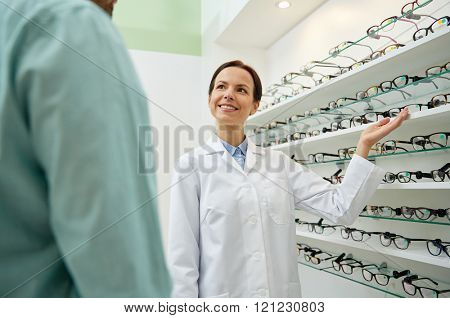health care, people, eyesight and vision concept - female optician showing glasses to man at optics store