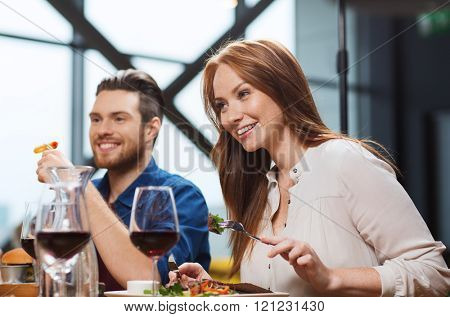 leisure, food and drinks, people and holidays concept - happy couple having dinner at restaurant