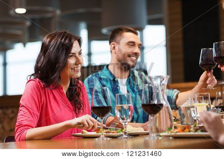 leisure, celebration, food and drinks, people and holidays concept - happy couple and friends clinking glasses of wine at restaurant