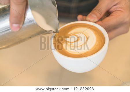 Pouring milk to mix Latte Coffee art