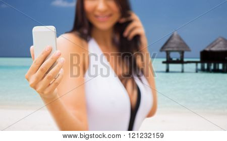 summer, travel, technology and people concept - close up of sexy young woman taking selfie with smartphone over bungalow on beach background