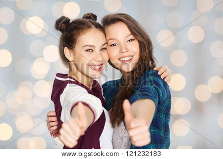 people, friends, teens and friendship concept - happy smiling pretty teenage girls hugging and showing thumbs up over holidays lights background