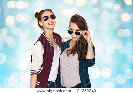 people, friendship, fashion, summer and teens concept - happy smiling pretty teenage girls in sunglasses over blue holidays lights background