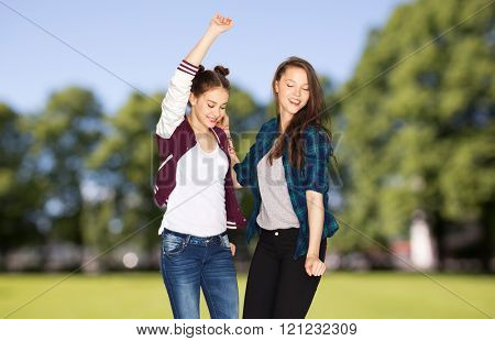 people, fun, teens and party concept - happy smiling pretty teenage girls dancing over summer park background