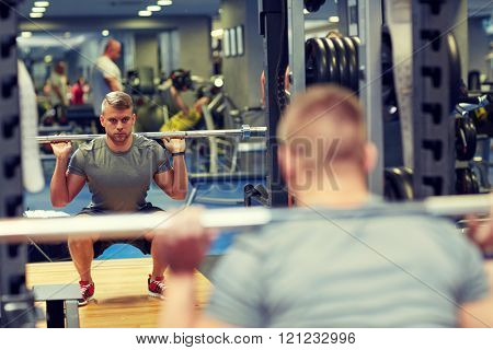 sport, fitness, bodybuilding, lifestyle and people concept - young man with barbell flexing muscles in gym