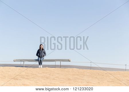 Woman sitting at bench with blue sky