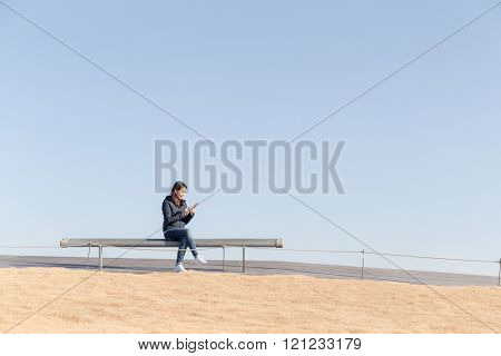 Woman using cellphone and sitting at bench with blue sky