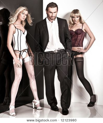Glamour style studio shot of a man and 2 women