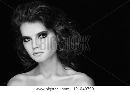 Black and white portrait of young beautiful woman with long curly hair and smoky eyes