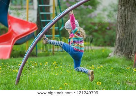 Active little girl climbing monkey bar outdoors on spring playground