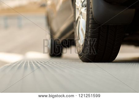 Dark automobile standing on steel floor view from below. Car parking problems motor show or exhibition winter season tires customer purpose loan vehicles official checkup or examination concept