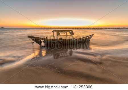Rotting boat catch the sunset on the beach with the ship disintegrated over time represents an aging generation to generation gave way to pay development. That is the law of life