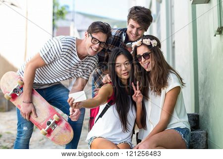 Hip friends taking selfie sitting on steps in the city