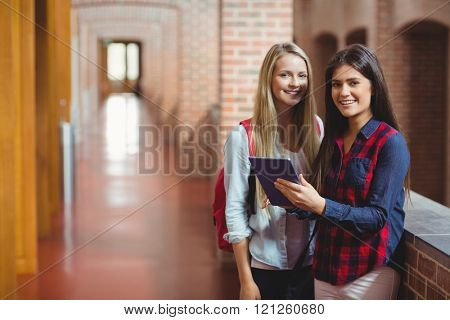 Smiling students using tablet together at university