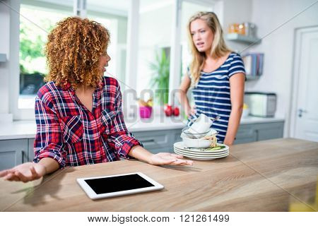 Upset woman showing dirty dishes to friend in kitchen poster