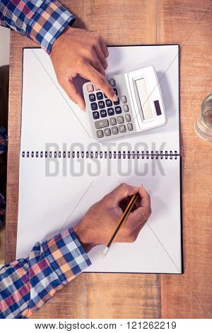Cropped image of businessman using calculator while writing on book at desk