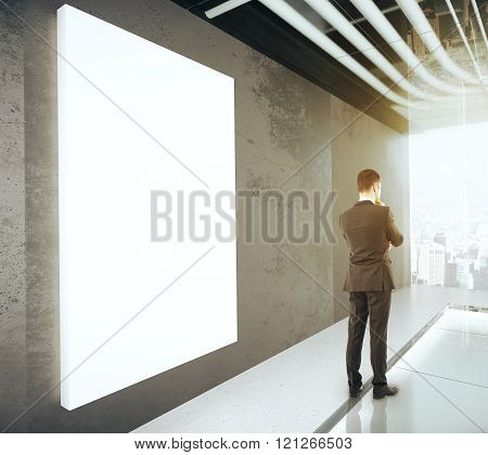 Businessman In Empty Modern Office Wiith Blank Poster On The Wall, Mock Up, 3D Render