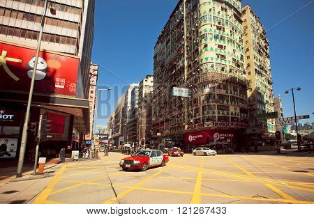 HONG KONG, CHINA - FEB 7: Broad street with skyscrapers and fast cornering taxi cab on February 7, 2016. Hong Kong dollar is the eighth most traded currency in the world.