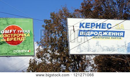 KHARKOV, UKRAINE - CIRCA OCTOBER 2015: The billboard of the candidate in mayors next to the advertisement, generating the second semantic plan, on the background of the autumn sky and trees.