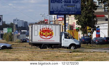 KHARKOV, UKRAINE - CIRCA OCTOBER 2015: Billboards on the background of urban development. Next is the van with the image of joyful chickens, creating a second semantic plan. In the background is a sign with the Ukrainian word-token -
