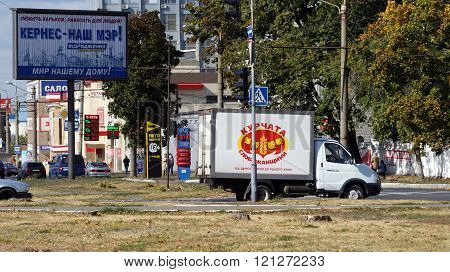 KHARKOV, UKRAINE - CIRCA OCTOBER 2015: Billboard on the background of urban development. Next is the van with the image of joyful chickens, creating a second semantic plan. In the background is a sign with the Ukrainian word-token -