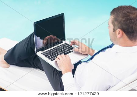 Smarty dressed using laptop near poolside while sitting on sun lounger