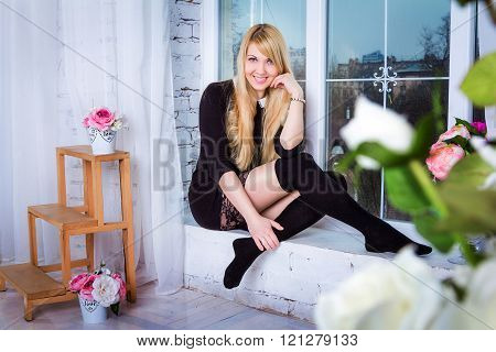 woman sitting on the window sill
