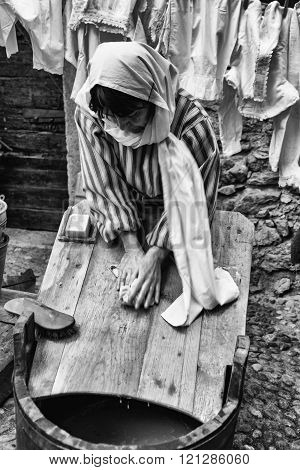 Washerwoman Washing Clothes On A Wooden Board.