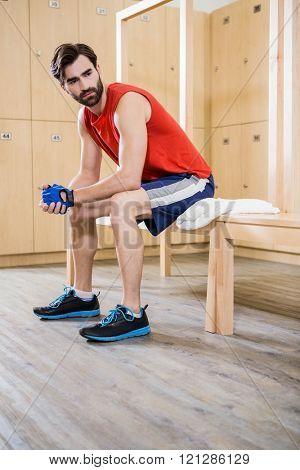 Unsmiling man sitting in locker room at the gym