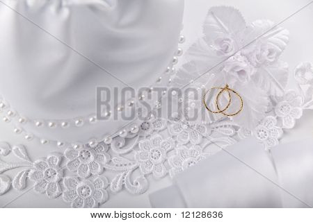 Wedding background with white silky decoration accessories and artificial golden rings