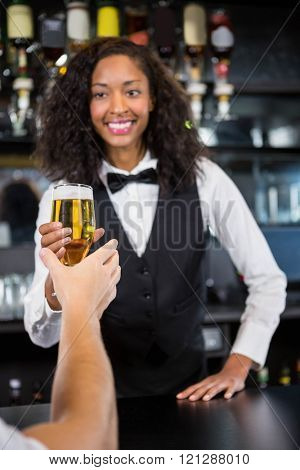 Beautiful barmaid serving glass of beer to man at bar counter in bar