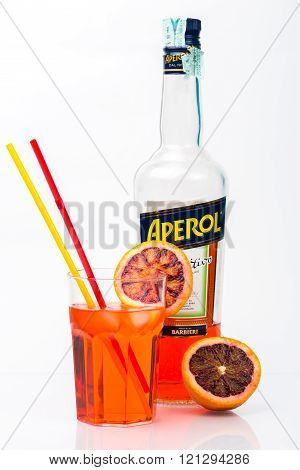 TRIESTE ITALY March 9 2016; Glass of light drink and ice cube with bottle of Aperol Aperitivo Poco Alcolico Liqueur alc.11%. Famous Italian aperitif. Produced by Fratelli Barbieri S.P.A. Italy