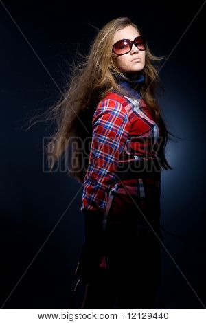 Beautiful fashion model with long hair in checkered dress and glasses