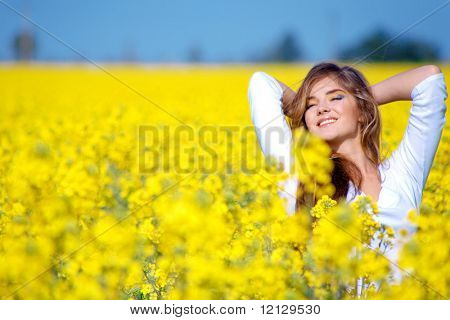 Beautiful woman standing in rape field and smiling