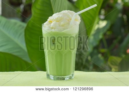 Cold Matcha green Tea fresh on the glass whipping cream topping