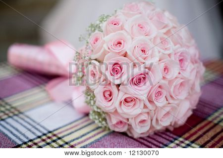 Wedding bouquet with pink roses on checkered backdrop