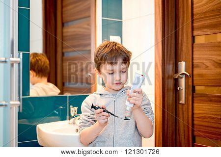 7 Years Old Boy Brushing His Teeth In The Bathroom