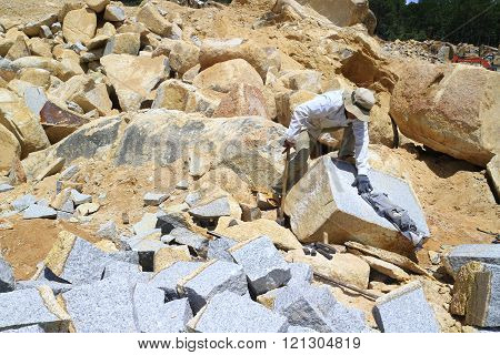 LAM DONG, VIET NAM- NOVEMBER 28: Worker with splitter on hand try to split stone into rectangle shape for road-works at mountain pass in Lam Dong, Viet Nam in May 24, 2015