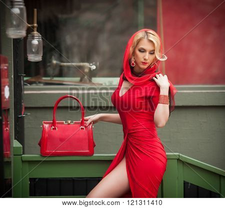 Charming young blonde with red dress, head scarf and bag. Sensual gorgeous young woman in red outfit