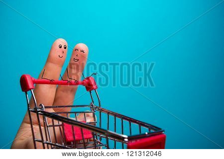 Funny fingers shopping at supermarket with red cart trolley on blue background