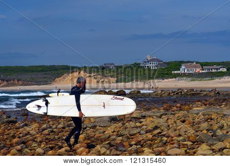 MONTAUK NEW YORK-JUNE 13: Unidentified senior surfer with surfboard on Ditch Plains surfing beach Altantic Ocean is seen on June 13 2015.